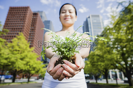 portrait woman holding green saplings in