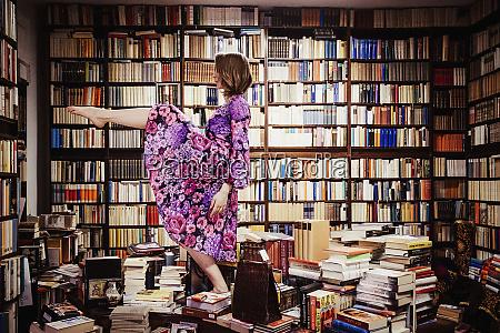 exuberant woman dancing on book stacks