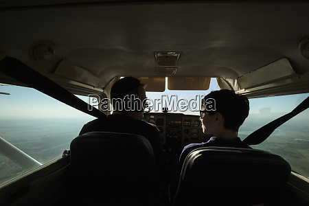 father and son flying in small