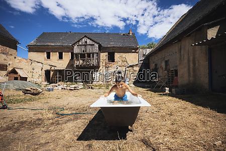 playful boy in bathtub on sunny