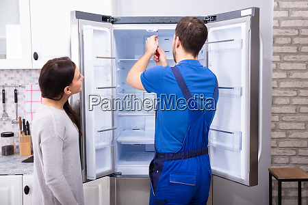 repairman fixing refrigerator with screwdriver