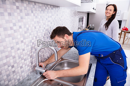 plumber fixing faucet in kitchen