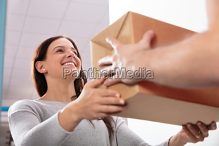 delivery, man, giving, box, to, young - 26416564