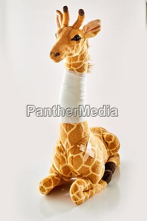 plush toy giraffe with bandaged neck