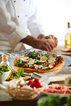 chef seasoning a pizza in a