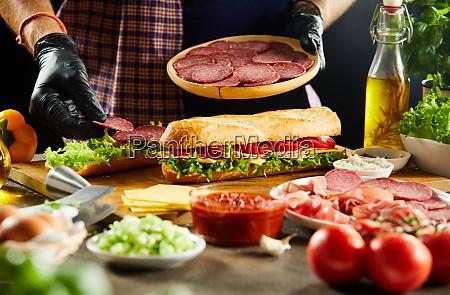 takeaway chef preparing baguette sandwiches