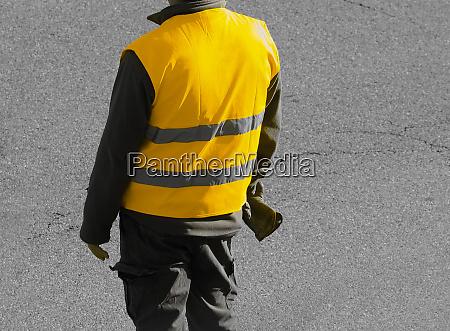 unrecognisable yellow vest person