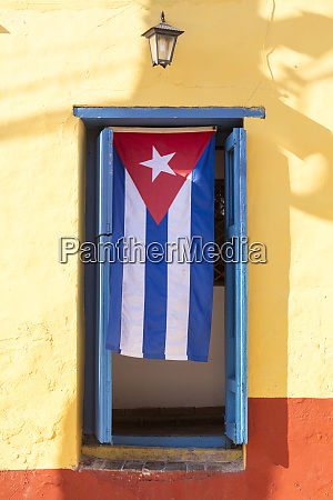 cuban flag in doorway trinidad unesco