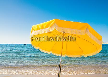 giant yellow beach umbrella next to