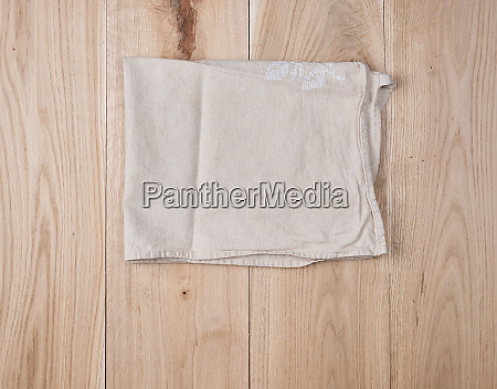 folded white towel on brown wooden