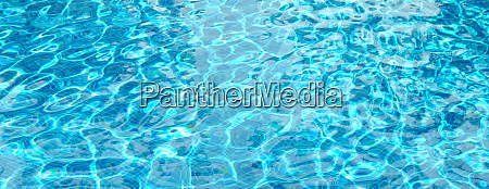 sun reflection in blue swimming pool