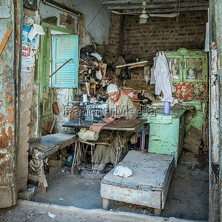 a poor egyptian tailor sewing in