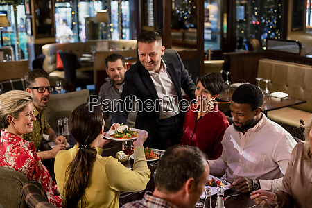 waiter passing a plate of food