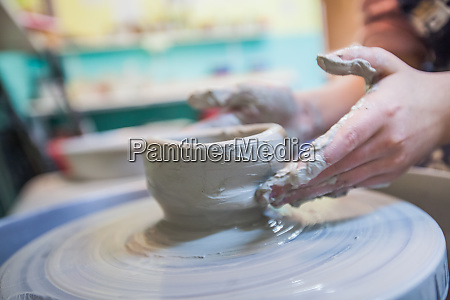child hands working with clay on