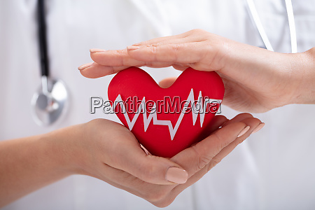 doctor protecting heart shape with heart