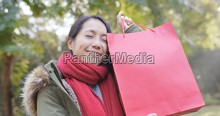 happy woman holding a red shopping