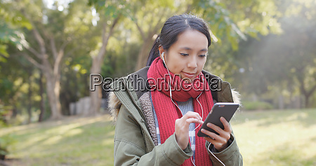 woman using smart phone with earphone