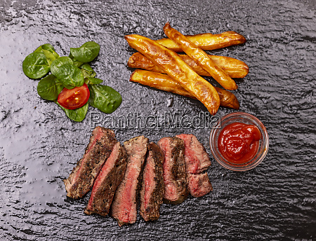 slices of steak with fries on
