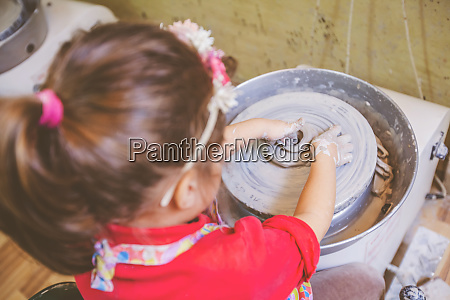 child learning new skill at pottery