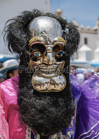 masked dancer in traditional costume fiesta