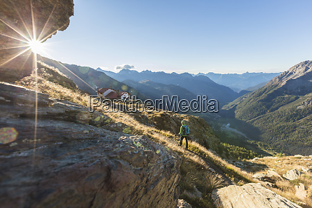 hiker on path towards rifugio longoni