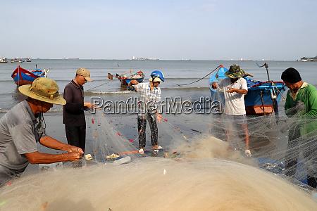 fishermen repairing fishing nets at tam