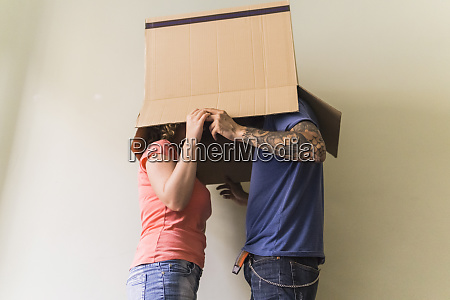 couple with heads together in cardboard