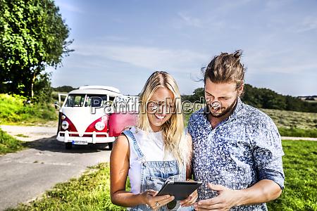 happy couple outside van in rural