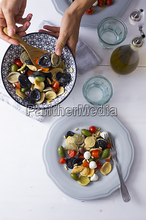 woman serving mediterranean orecchiette with tomato