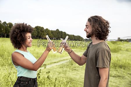 happy couple clinking beer bottles in