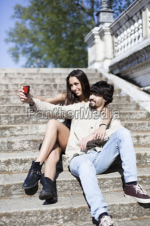 happy young couple sitting on stairs