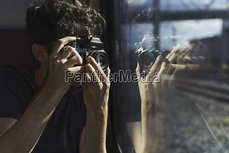 man traveling by train taking picture