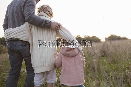 father with two children standing at