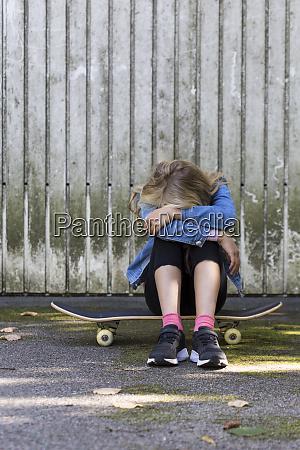 girl sitting on her skateboard outdoors