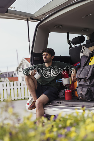 young man sitting in camper preparing