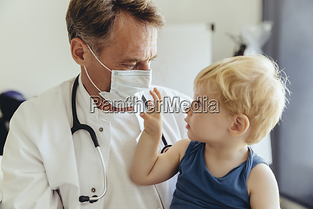 toddler sitting on lap of pediatrician