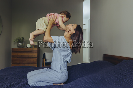 mother lifting up her baby girl