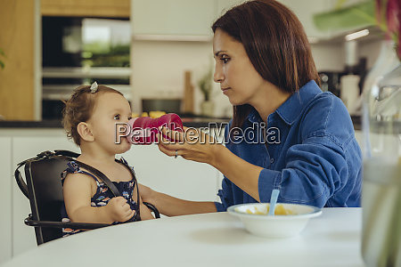 mother helping baby daughter drinking water