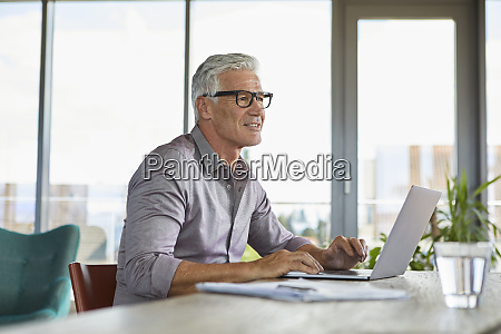 mature man using laptop on table