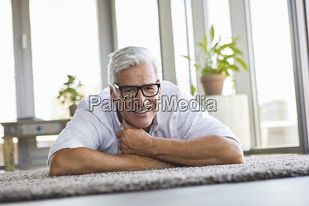 smiling mature man relaxing lying on