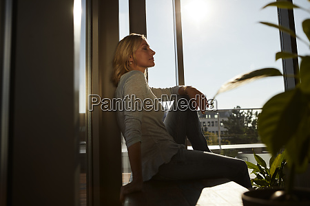 relaxed mature woman sitting in sunlight