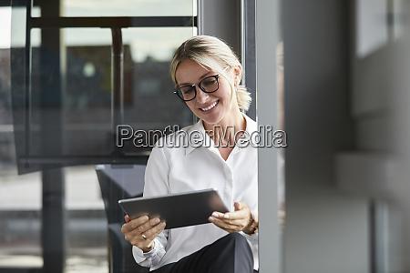 serene businesswoman sitting on ground in