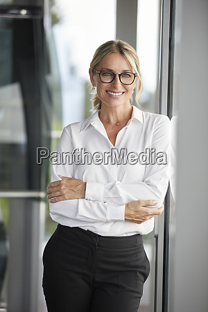 businesswoman in office leaning against window
