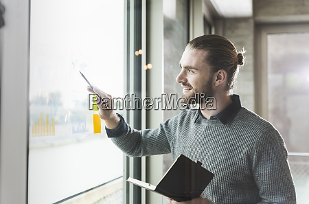 smiling young businessman working on data