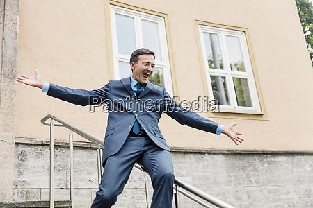 carefree businessman sliding down railing in