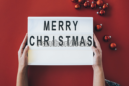 womans hands holding merry christmas sign