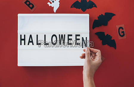 womans hands adding letter at halloween