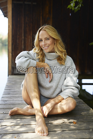 smiling relaxed woman sitting on wooden