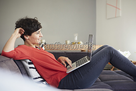 smiling woman using laptop on couch