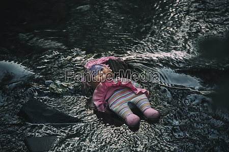 doll lying in brook